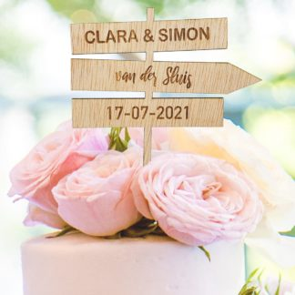 taarttoper in de vorm van wegwijzerbord voor trouwen